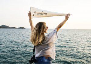 Kvinde står med flag, hvor der står freedom